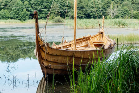 old wooden viking boat by the lake on sunny summer day Stock Photo