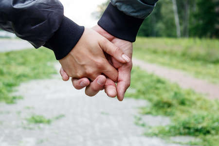 woman with a man holding a hand outdoor on summer day. hands closeup