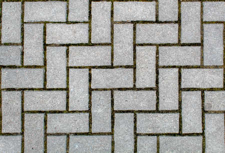 road paved with sidewalk tiles. beautiful brick background with, masonry texture of light gray bricks. outdoor closeup