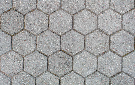 road paved with hexagonal sidewalk tiles. beautiful brick background with, masonry texture of light gray bricks. outdoor closeup