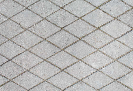 road paved with rhombus sidewalk tiles. beautiful brick background with, masonry texture of light gray bricks. outdoor closeup