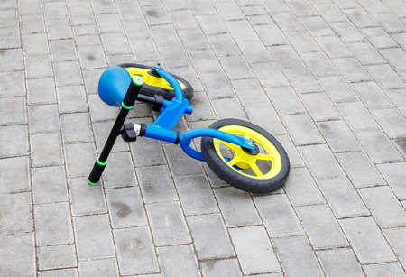 blue children bicycle lying on the sidewalk on summer day Stock Photo