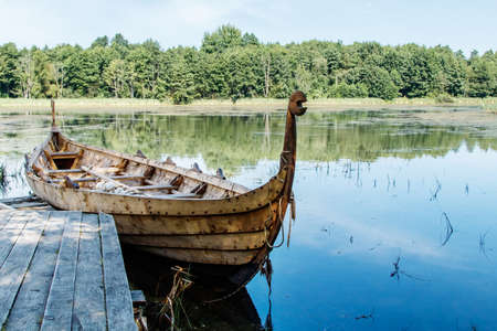 old wooden viking boat by the lake on sunny summer day Standard-Bild