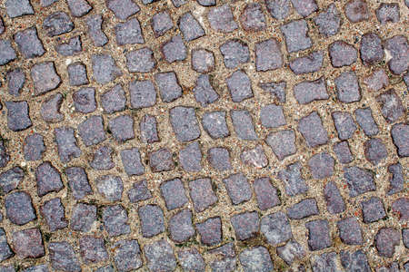 pavement of granite stone.old cobblestone road pavement texture. absrtact background. outdoor closeup Stock Photo