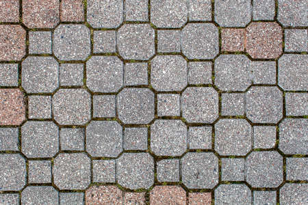 road paved with sidewalk tiles. beautiful brick background with, masonry texture of light brown and gray bricks. outdoor closeup