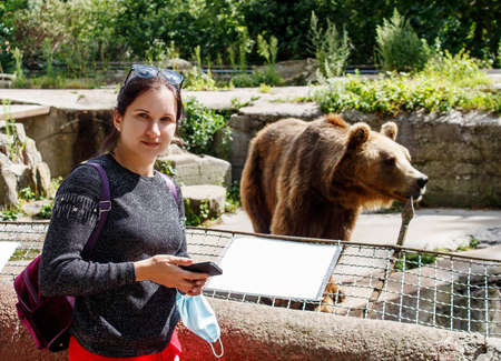 girl photographs a bear in city zoo with a smartphone on sunny summer day