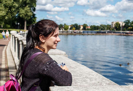 young brunette girl looking at the lake in the city park on sunny summer day Standard-Bild
