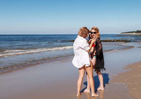 two girls in swimsuits take pictures of each other with smartphone on the seashore on sunny summer day