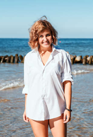 young blonde smiling woman in a white swimsuit and shirt posing standing on the seashore on sunny summer day