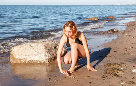 young girl in a swimsuit drawing with her finger on the sand by the seashore on sunny summer day Standard-Bild