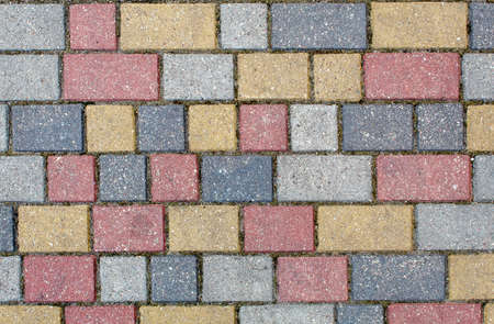 road paved with sidewalk tiles. beautiful brick background with, masonry texture of light brown, yellow and gray bricks. outdoor closeup Stock Photo