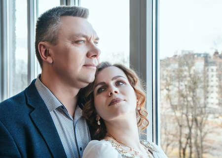 married couple standing by the window indoor in their home Standard-Bild