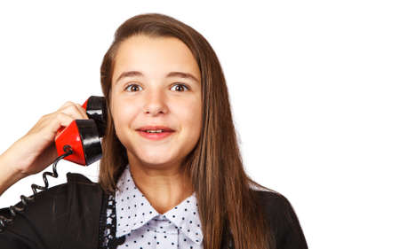 teenage surprised brunette girl talking on red retro telephone closeup on white background Standard-Bild