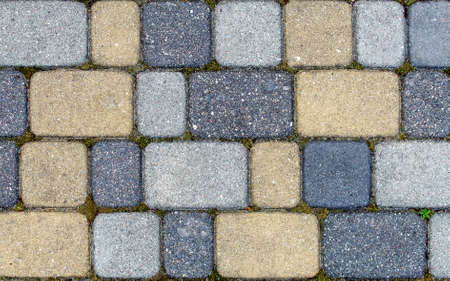 road paved with sidewalk tiles. beautiful brick background with, masonry texture of yellow light and dark gray bricks. outdoor closeup