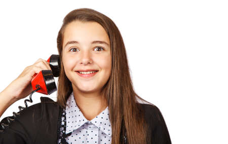 teenage surprised brunette girl talking on red retro telephone closeup on white background Stock Photo