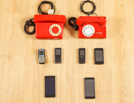 set of various old phones and modern smartphones on yellow wooden background. conceptual photo