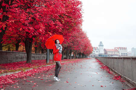 young girl in a red coat with an umbrella stands on the alley of the park after the rain on an autumn day Archivio Fotografico