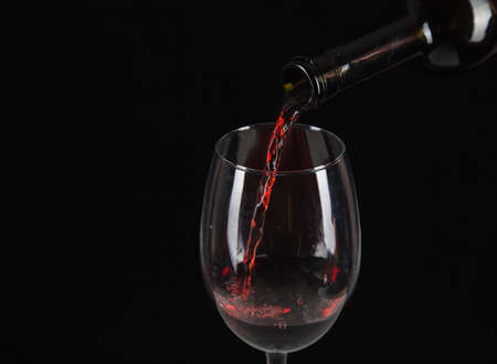 red wine is poured into a glass closeup on black background Standard-Bild