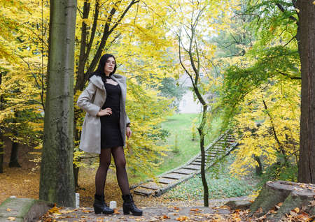 young girl in a gray coat stands on an alley in a city park on an autumn day