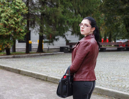 lonely young girl in a brown jacket and black jeans standing on the sidewalk on autumn day