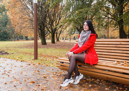 young beautiful girl in a red coat sitting on a bench in a city park after the rain on an autumn day Standard-Bild
