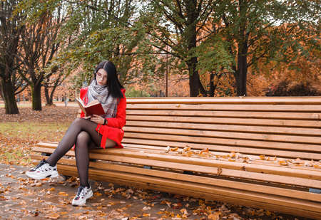 young beautiful girl in red coat reading book while sitting on a park bench on autumn day