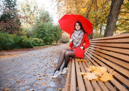 young girl in a red coat with an umbrella sitting on a bench in a city park after the rain on an autumn day Standard-Bild