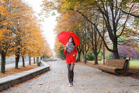 young girl in a red coat with an umbrella walking on the alley of a city park on a sunny autumn day