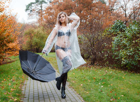 young woman in black lingerie, stockings and a transparent raincoat with umbrella standing on the alley in the park on an autumn day