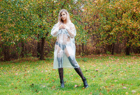 young woman in black lingerie, stockings and a transparent raincoat standing on the alley in the park on an autumn day Standard-Bild