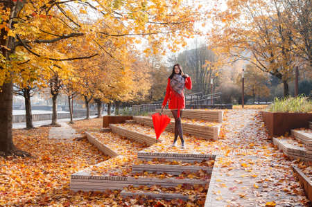 young girl in a red coat with an umbrella standing on the alley of a city park on a sunny autumn day