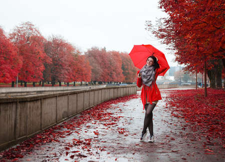 young smiling girl in a red coat with an umbrella stands on the alley of the park after the rain on gloomy autumn day