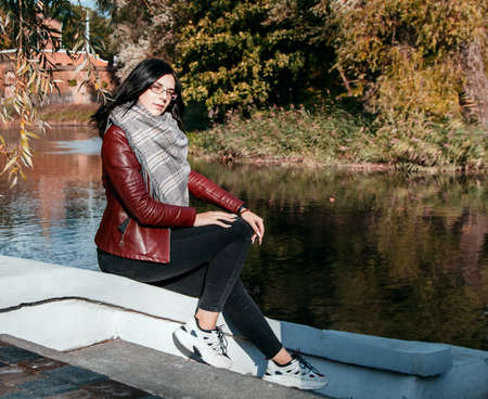 young girl in brown jacket and black jeans sitting on a parapet near a pond in city park on sunny autumn day
