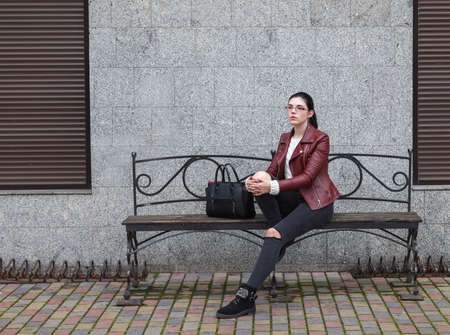 lonely young girl in a brown jacket and black jeans sitting on a bench near the sidewalk on gloomy autumn day