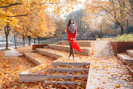 young smiling girl in a red coat with an umbrella standing on the alley of a city park on a sunny autumn day