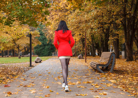 young girl in a red coat walking on an alley in a city park on an autumn day. back view
