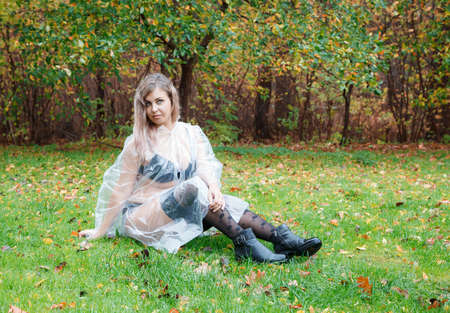 young woman in black lingerie, stockings and a transparent raincoat sitting on the grass in the park on an autumn day. portrait closeup