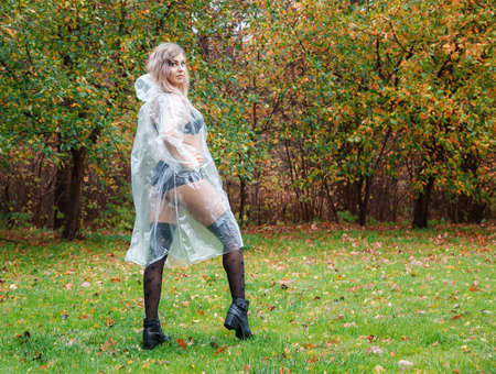 young woman in black lingerie, stockings and a transparent raincoat walking in the park on an autumn day Standard-Bild