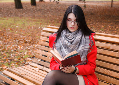 young beautiful girl in red coat reading book while sitting on a park bench on autumn day. portrait closeup
