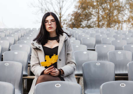 lonely young girl in a gray coat sitting on a seat of an empty stadium on autumn day