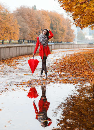 young girl in a red coat with an umbrella stands on the alley of the park after the rain on gloomy autumn day