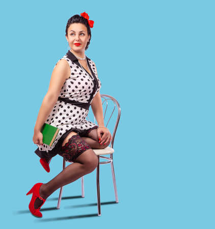 young brunette woman holds book sitting on a chair in studio. pinup style