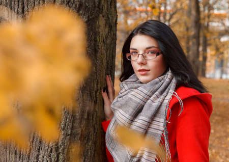 portrait of young girl in a red coat standing on the alley of the park on an autumn day Standard-Bild