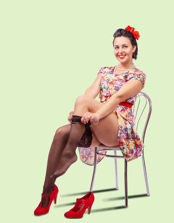 woman straightens her stocking while sitting on a chair in studio. pinup style