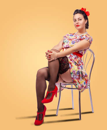 young brunette woman posing sitting on a chair in studio. pinup style