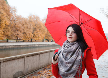 portrait of young smiling girl in a red coat with an umbrella standing on the alley of the park after the rain on gloomy autumn day