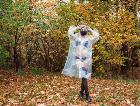 young woman in black lingerie, stockings, protective mask and a transparent raincoat standing on the alley in the park on an autumn day Standard-Bild