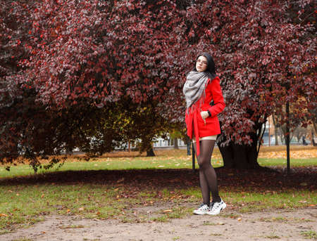 young girl in a red coat standing on the alley of a city park on a autumn day