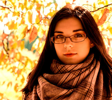portrait of a young beautiful girl in brown jacket in city park on sunny autumn day Standard-Bild