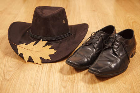 set of men's felt hat with a yellow maple leaf and black shoes on a wooden floor